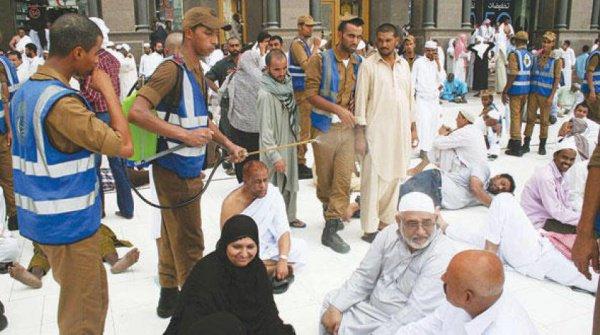 Сотрудники Запретной мечети помогают паломникам в жару.