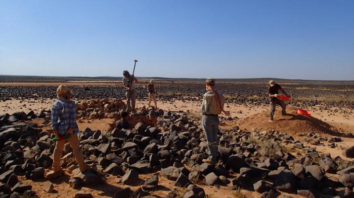 Команда Globalkites работает на земле рядом с воздушным змеем.