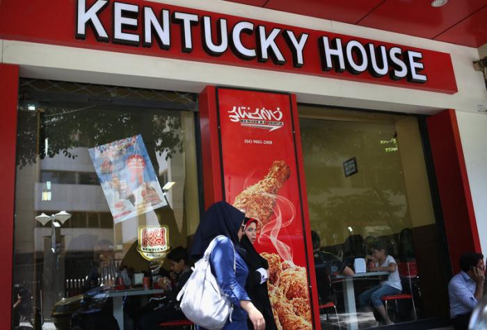 Женщины проходят мимо ресторана быстрого питания с жареной курицей в Исфахане, Иран.