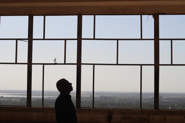 Человек стоит перед окном в заброшенном дворце Саддама Хусейна