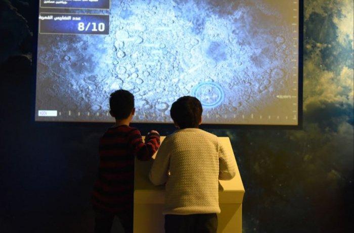 Дети открывают лунные образования в интерактивной лунной игре на выставке 1001 изобретение