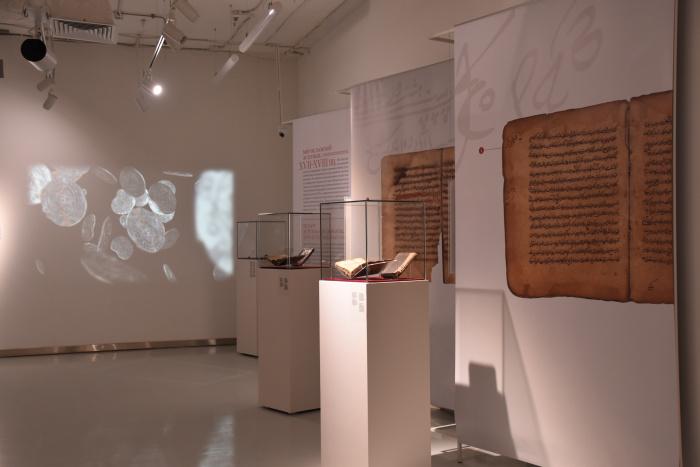 Видеопроекции с монетами, витрины с рукописями и текстами.