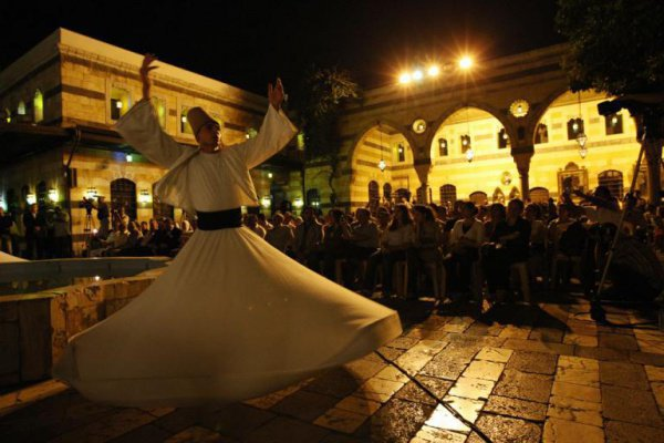 2008 г. Покупатели рынка в Алеппо наблюдают за танцем дервиша
