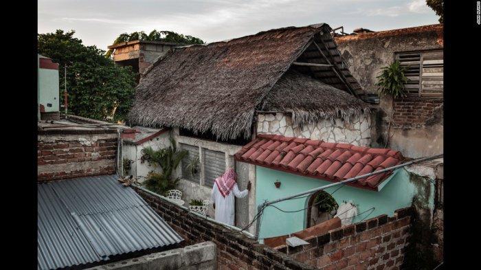 Мусульманин входит в местную мечеть, построенную как и все здания на Кубе - каменная коробка, перекрытая пальмовыми листьями.