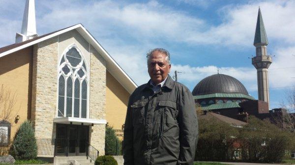 Глава мусульманской общины Наим Малик на фоне зданий церкви и мечети.