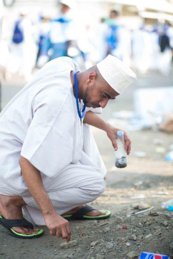 Паломник из Омана подбирает камни для обряда побивания шайтана