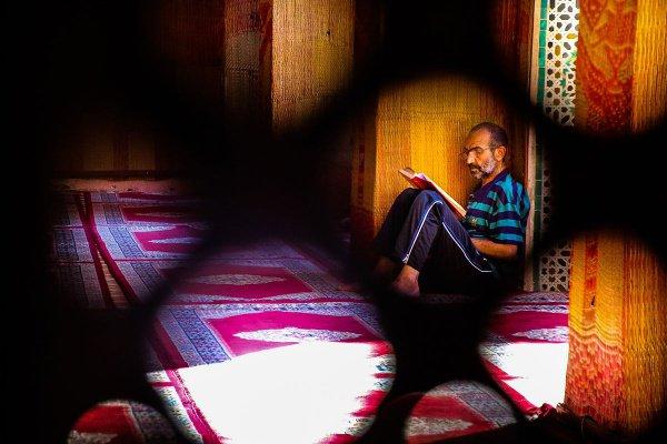 Мужчина читает Коран в медресе