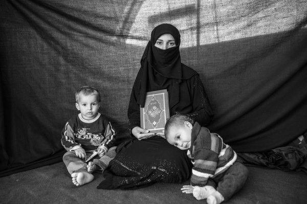 Коран: 25-летняя Иман вместе с сыном Ахмедом и дочкой Аишей в лагере беженцев в Турции с кораном в руках, говорит, что Он дает ей чувство безопасности