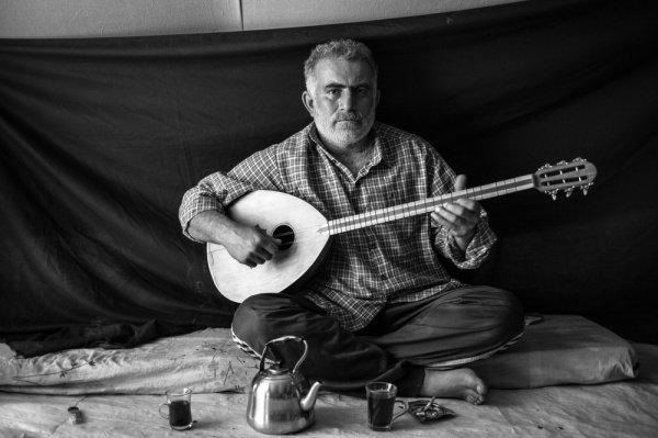 Бузук: 37-летний Омар держит в руках разновидность лютни, известной как бузук, который он привез с собой в Домиз из Дамаска