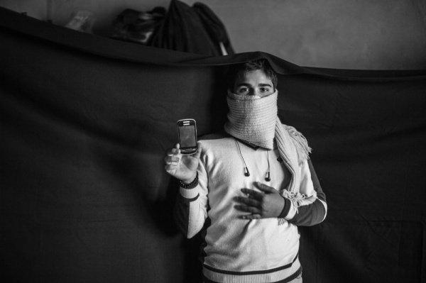 Телефон: Йусуф в ливийском лагере держит в руках самое ценное для него – свой телефон, по которому он звонит своему отцу, который по-прежнему находится в Сирии и смотрит фотографии своей семьи