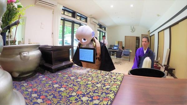 Робот-священник выполняет погребальный обряд.