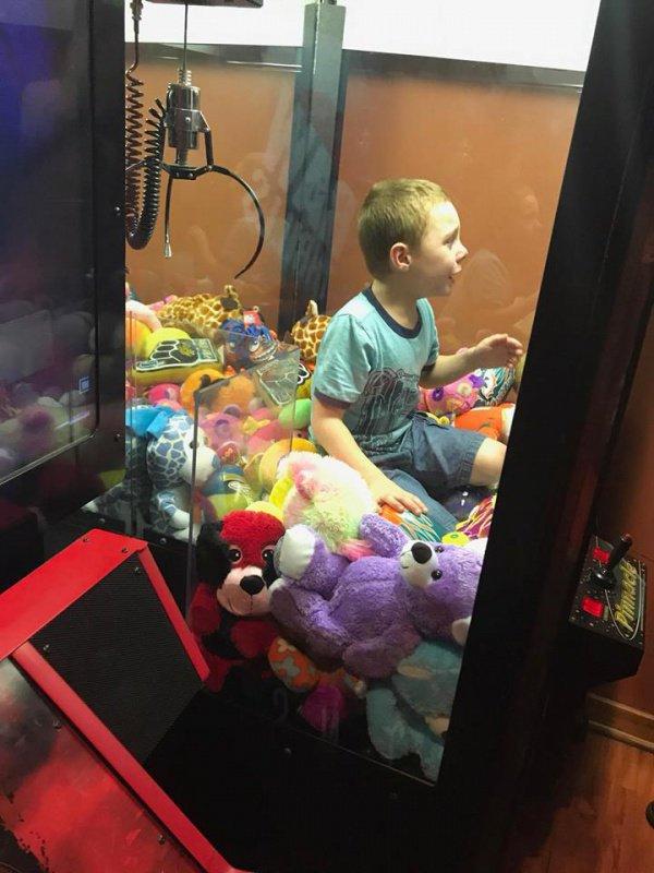 Мальчик влез внутрь машины сквозь отверстие, куда обычно выпадает приз