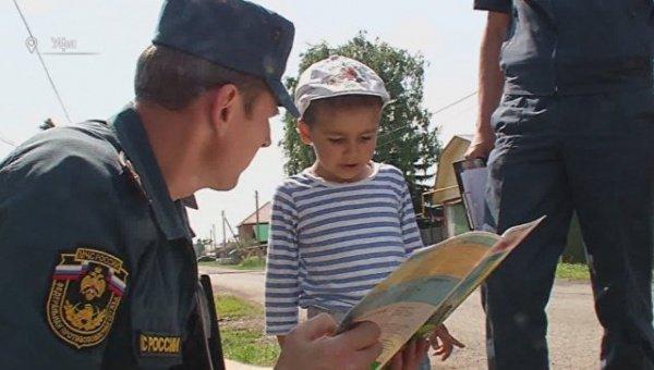 Маленький герой с благодарными пожарными.