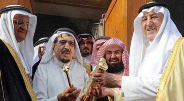 Во время установки нового замка на двери Каабы. Шейх Абдулькадир аль-Шайби получает замок из рук принца Мекки Халида аль-Файсала