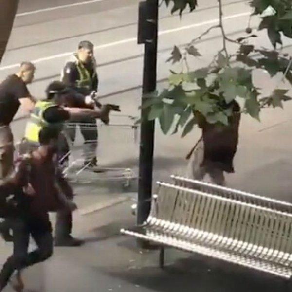 Майкл Роджерс с тележкой (слева) пытается остановить террориста вместе с полицейскими.
